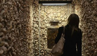 In this Thursday, Nov. 16, 2017 photo a woman examines an old metal milk bottle at a Holocaust exhibition at the Jewish Historical Institute in Warsaw, Poland. Letters and other eyewitness accounts of Jews in the Warsaw Ghetto _ records of a community destroyed in the Holocaust _ have gone on display for the first time. (AP Photo/Alik Keplicz)