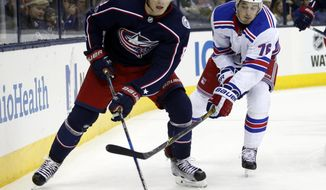 Columbus Blue Jackets defenseman Zach Werenski, left, controls the puck against New York Rangers defenseman Brady Skjei during the first period of an NHL hockey game in Columbus, Ohio, Friday, Nov. 17, 2017. (AP Photo/Paul Vernon)