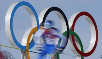 In this Feb. 23, 2014, file photo taken with slow shutter speed, athletes pass the Olympic rings during the men's 50K cross-country race at the 2014 Winter Olympics in Krasnaya Polyana, Russia. World Anti-Doping Agency investigations into doping haven't encouraged Russian athletes to speak out about abuses, but instead, there is a public hunt for whistleblowers, as Tuesday Nov. 14, 2017, Russia seems to move closer to a ban from the upcoming Winter Olympics. (AP Photo/Dmitry Lovetsky, FILE)