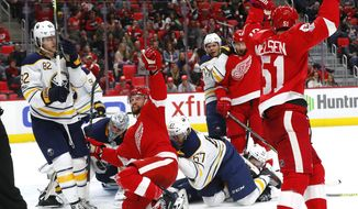 Detroit Red Wings right wing Luke Glendening, kneeling middle, celebrates his goal against the Buffalo Sabres during the second period of an NHL hockey game Friday, Nov. 17, 2017, in Detroit. (AP Photo/Paul Sancya)