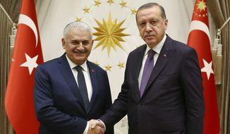 Turkey's President Recep Tayyip Erdogan, right, shakes hands with Turkey's Prime Minister Binali Yildirim, left, prior to their meeting in Ankara, Turkey, Thursday, Nov. 16, 2017. (Kayhan Ozer/Pool via AP)