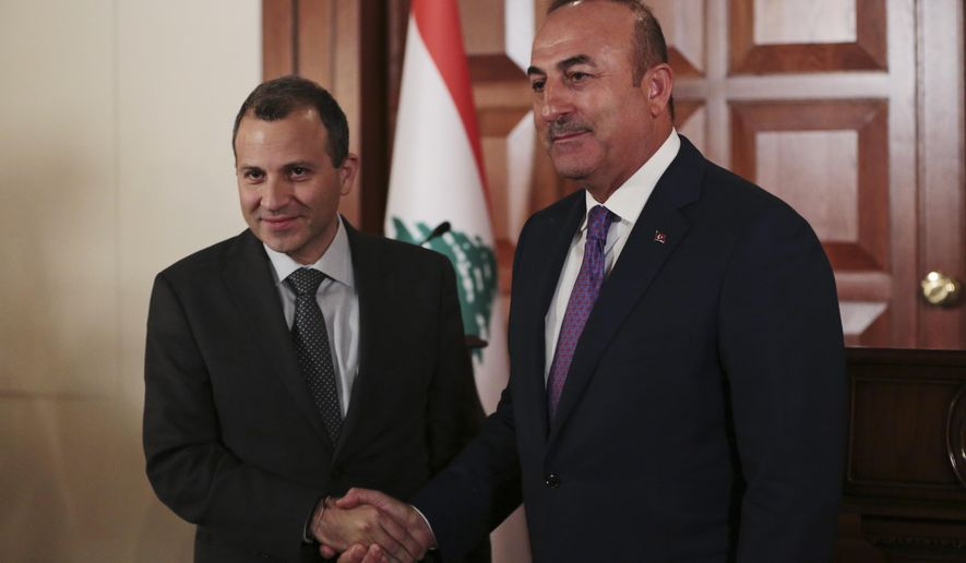 Lebanon's Foreign Minister Gebran Bassil, left, shakes hands with his Turkish counterpart Mevlut Cavusoglu, right, after their joint news conference following their meeting in Ankara, Turkey, Thursday, Nov. 16, 2017. (AP Photo/Burhan Ozbilici)