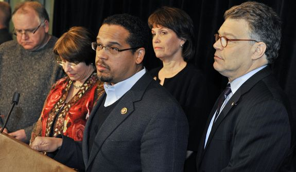 Sen. Al Franken, right, listens as Rep. Keith Ellison, third from left, is joined by from left, Rep. Tim Walz, Sen. Amy Klobuchar and Rep. Betty McCollum the Minnesota congressional delegation gathered to talk about the shootings in Arizona that included the wounding of their colleague, Rep. Gabrielle Giffords earlier Saturday in Tucson. The delegation, on hand for Minnesota Gov. Mark Dayton's inaugural ball Saturday, Jan. 8, 2011 in Minneapolis, included from left, Sen. Amy Klobuchar, Rep. Tim Walz (partially hidden), Rep. Betty McCullum and right, Rep. Keith Ellison. (AP Photo/Jim Mone)