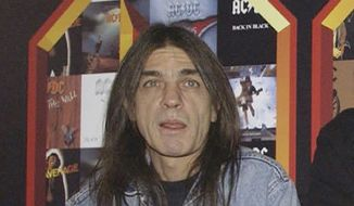 A March 3, 2003 file photo of AC/DC co-founder and guitarist Malcolm Young at an event in London. The band has announced, Saturday Nov. 18, 2017,  that 64-year-old Young has died. (Yui Mok/PA via AP)