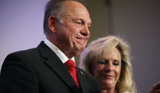 """In this Nov. 16, 2017, photo, former Alabama Chief Justice and U.S. Senate candidate Roy Moore speaks at a news conference in Birmingham, Ala., with his wife Kayla Moore, right. A sex scandal has relegated Moore's hard-line positions on LGBT issues to the background in Alabama's turbulent Senate race even as religious activists blame the """"LGBT mafia"""" and """"homosexualist gay terrorism"""" for his precarious political plight. (AP Photo/Brynn Anderson)"""