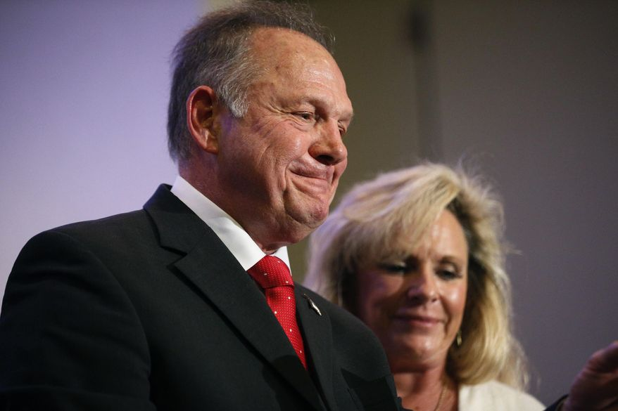 In this Nov. 16, 2017, photo, former Alabama Chief Justice and U.S. Senate candidate Roy Moore speaks at a news conference in Birmingham, Ala., with his wife Kayla Moore, right. (AP Photo/Brynn Anderson)
