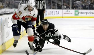 Los Angeles Kings left wing Andy Andreoff, right, dives for the puck past Florida Panthers defenseman Aaron Ekblad during the third period of an NHL hockey game in Los Angeles, Saturday, Nov. 18, 2017. (AP Photo/Chris Carlson)