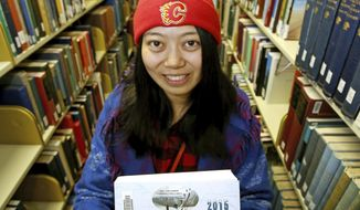 In this Wednesday, Nov. 8, 2017 photo, former University of Alaska Fairbanks student Qingping Yu displays a book in the UAF Rasmuson Library in Fairbanks, Alaska. Yu, who has met some of the best skiers in the world through her work in the international alpine skiing industry, is now preparing China for the Beijing 2022 Winter Olympics as the sports manager for the game's freestyle ski and snowboard programs. (Eric Engman/Fairbanks Daily News-Miner via AP)