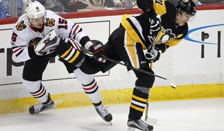 Pittsburgh Penguins' Evgeni Malkin (71) loses control of the puck as he collides with Chicago Blackhawks' Artem Anisimov (15) during the first period of an NHL hockey game in Pittsburgh, Saturday, Nov. 18, 2017. (AP Photo/Gene J. Puskar)