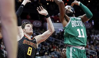 Boston Celtics' Kyrie Irving, right, passes the ball behind himself and over Atlanta Hawks' Luke Babbitt in the second quarter of an NBA basketball game in Atlanta, Saturday, Nov. 18, 2017. (AP Photo/David Goldman)