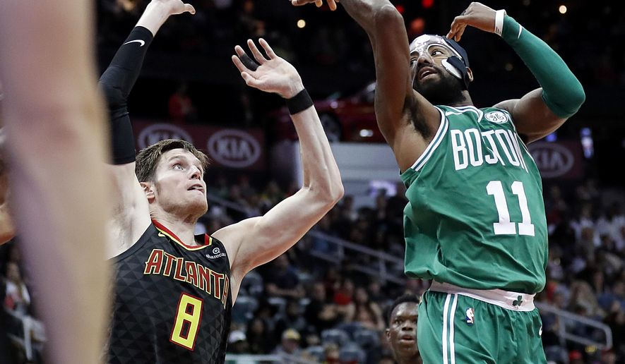 Boston Celtics' Kyrie Irving, right, passes the ball behind himself and over Atlanta Hawks' Luke Babbitt in the second quarter of an NBA basketball game in Atlanta, Saturday, Nov. 18, 2017. (AP Photo/David Goldman)