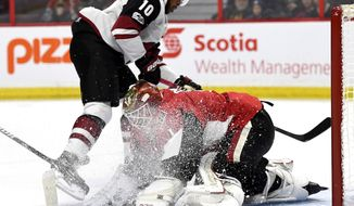 Ottawa Senators goaltender Mike Condon (1) is showered in ice as Arizona Coyotes' Anthony Duclair (10) scores against him during the first period of an NHL hockey game in Ottawa, Saturday, Nov. 18, 2017. (Justin Tang/The Canadian Press via AP)