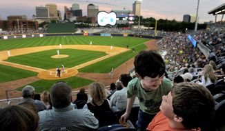 In this April 17, 2015 photo, friends Frank Hancock, 10, and Alex Humphrey, 11, who have gone to all the past Nashville Sounds game, celebrating opening day at First Tennessee Park in Nashville in Tenn.  Subsidies by Metro Nashville government to First Tennessee Park, home of the Nashville Sounds minor league baseball team, are expected to be greater than the amount estimated when the ballpark was pitched in 2013, thanks in part to the delayed development of adjacent real estate. (John Partipilo/The Tennessean via AP)