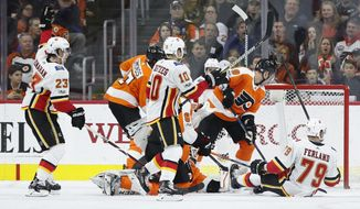 Calgary Flames' Sean Monahan, left, reacts to his goal during the second period of an NHL hockey game against the Philadelphia Flyers, Saturday, Nov. 18, 2017, in Philadelphia. (AP Photo/Chris Szagola)