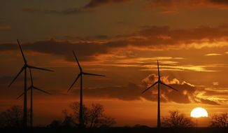 The sun sets behind wind turbines near Pokrent, northern Germany, Friday, Nov. 17, 2017. (Jens Buettner/dpa via AP)