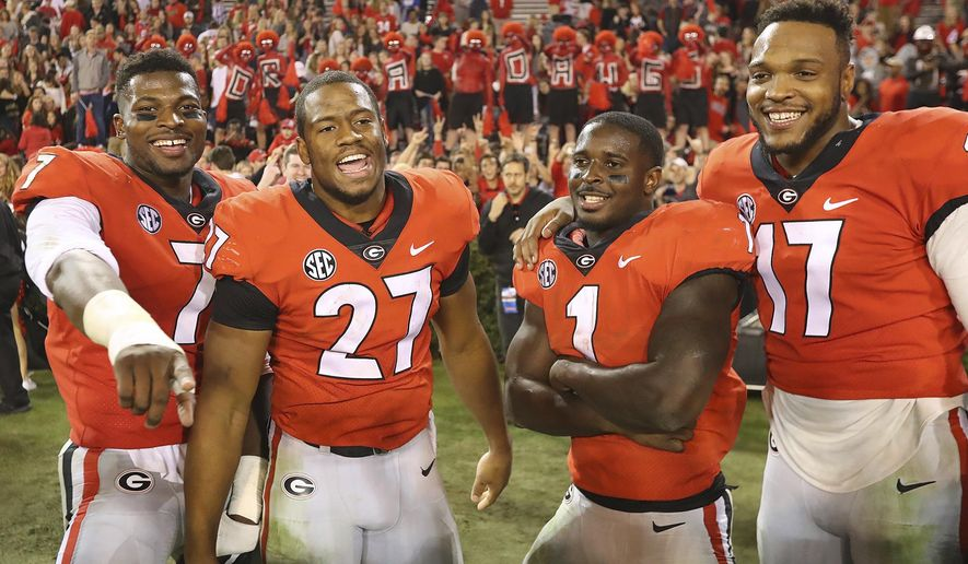 Georgia seniors, from left, Lorenzo Carter, Nick Chubb, Sony Michel, and Davin Bellamy celebrate their 42-13 victory over Kentucky  in an NCAA college football game, Saturday, Nov. 18, 2017, in Athens, Ga. (Curtis Compton/Atlanta Journal-Constitution via AP)