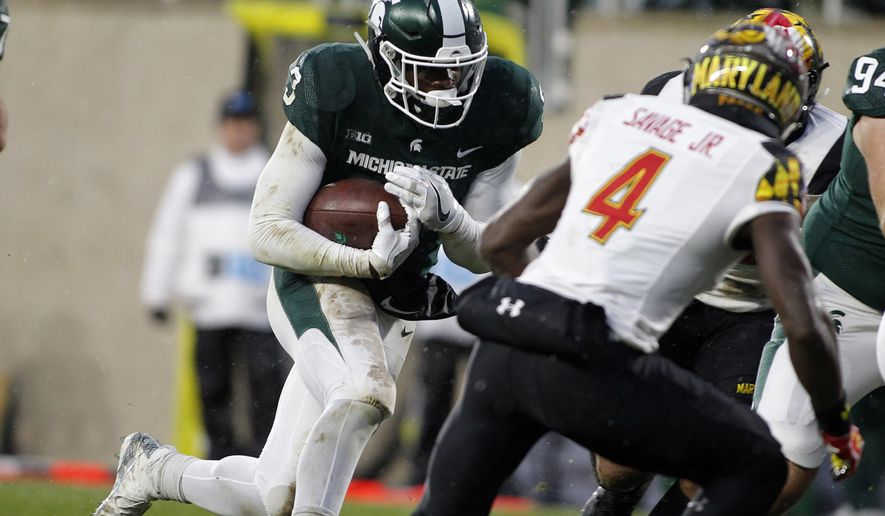 Michigan State's LJ Scott, left, runs for a touchdown against Maryland's Darnell Savage Jr. (4) during the first half of an NCAA college football game, Saturday, Nov. 18, 2017, in East Lansing, Mich. (AP Photo/Al Goldis)