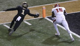 Wake Forest's Tabari Hines (1) reaches for the goal line as North Carolina State's Chris Ingram (15) defends during the first half of an NCAA college football game in Winston-Salem, N.C., Saturday, Nov. 18, 2017. Hines scored on the play. (AP Photo/Chuck Burton)