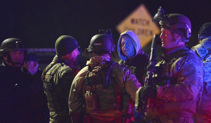 SWAT team members prepare to search the neighborhood where a police officer was fatally shot Friday, Nov. 17, 2017, in New Kensington, Pa. Authorities in Pennsylvania say a police officer was shot and killed while making a traffic stop and a search is underway for the gunman. (Rebecca Droke/Pittsburgh Post-Gazette via AP)