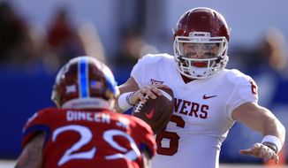 Oklahoma quarterback Baker Mayfield (6) tries to avoid Kansas linebacker Joe Dineen Jr. (29) during the first half of an NCAA college football game in Lawrence, Kan., Saturday, Nov. 18, 2017. (AP Photo/Orlin Wagner) **FILE**