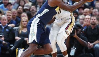 Denver Nuggets forward Paul Millsap, front, drives the lane past New Orleans Pelicans guard Jrue Holiday in the first half of an NBA basketball game Friday, Nov. 17, 2017, in Denver. (AP Photo/David Zalubowski)