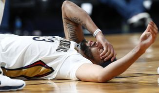 New Orleans Pelicans forward Anthony Davis holds his forehead after getting hit by Denver Nuggets center Nikola Jokic during the second half of an NBA basketball game Friday, Nov. 17, 2017, in Denver. Davis left the game. The Nuggets won 146-114. (AP Photo/David Zalubowski)