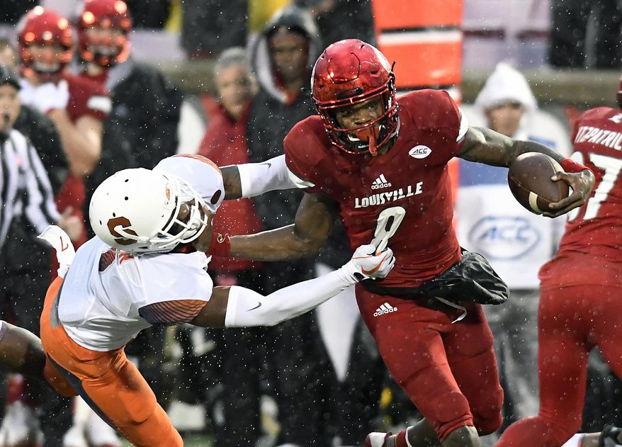 Louisville quarterback Lamar Jackson (8) runs from the grasp of Syracuse defensive back Devin M. Butler (7) during the first half of an NCAA college football game, Saturday, Nov. 18, 2017, in Louisville, Ky. (AP Photo/Timothy D. Easley)