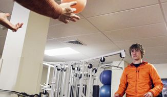 In this Nov. 9, 2017 photo, Nick Daugherty plays catch with a ball during a physical therapy session at the St. Luke Community Clinic in Ronan, Mont.  Daugherty's life changed after suffering concussion. (Greg Lindstrom/Flathead Beacon via AP)