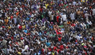An army soldier, centre right, pleads with thousands of protesters demanding President Robert Mugabe stand down, to keep their calm and not try to surge forward, as they gather behind an army cordon on the road leading to State House in Harare, Zimbabwe Saturday, Nov. 18, 2017. In a euphoric gathering that just days ago would have drawn a police crackdown, crowds marched through Zimbabwe's capital on Saturday to demand the departure of President Robert Mugabe, one of Africa's last remaining liberation leaders, after nearly four decades in power. (AP Photo/Ben Curtis)