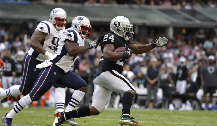 Oakland Raiders running back Marshawn Lynch (24) rushes past New England Patriots linebacker David Harris, center, during the first half of an NFL football game Sunday, Nov. 19, 2017, in Mexico City. (AP Photo/Rebecca Blackwell)
