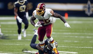 Washington Redskins tight end Vernon Davis (85) carries as New Orleans Saints free safety Vonn Bell (48) tries to tackle in the first half of an NFL football game in New Orleans, Sunday, Nov. 19, 2017. (AP Photo/Butch Dill)