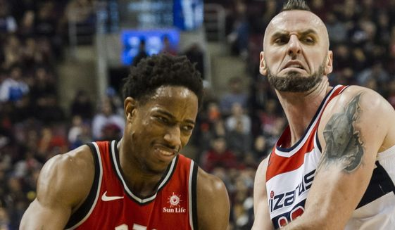 Toronto Raptors guard DeMar DeRozan (10) dribbles past Washington Wizards center Marcin Gortat (13) in first-half NBA basketball game action in Toronto, Sunday, Nov. 19, 2017. (Christopher Katsarov/The Canadian Press via AP)