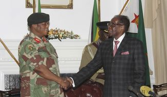 Zimbabwean President Robert Mugabe, right, shakes hands with Army General Constantino Chiwenga before delivering his speech during a live broadcast at State House in Harare, Sunday, Nov, 19, 2017. Zimbabwe's President Robert Mugabe has baffled the country by ending his address on national television without announcing his resignation. (AP Photo)