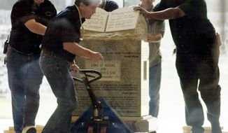 In this Wednesday, Aug. 27, 2003 file photo, workers move the Ten Commandments monument from the rotunda of the Alabama Judicial Building in Montgomery, Ala. The monument will be displayed beginning Tuesday, Feb. 11, 2020, in Montgomery at the Foundation for Moral Law, a conservative nonprofit that former Alabama Supreme Court Chief Justice Roy Moore started with his wife, Kayla, in 2003. (AP Photo/Bill Haber) **FILE**