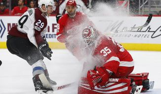 Colorado Avalanche center Nathan MacKinnon (29) sprays Detroit Red Wings goalie Jimmy Howard (35) with ice while having his shot blocked in the second period of an NHL hockey game Sunday, Nov. 19, 2017, in Detroit. (AP Photo/Paul Sancya)