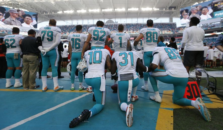 Miami Dolphins wide receiver Kenny Stills (10), free safety Michael Thomas (31) and tight end Julius Thomas (89), kneel during the National Anthem behind their teammates before an NFL football game against the Tampa Bay Buccaneers, Sunday, Nov. 19, 2017, in Miami Gardens, Fla. (AP Photo/Wilfredo Lee)