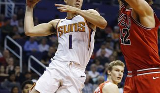 Phoenix Suns guard Devin Booker (1) looks to pass the ball as Chicago Bulls center Robin Lopez (42) defends while Bulls' Lauri Markkanen, middle, watches during the first half of an NBA basketball game Sunday, Nov. 19, 2017, in Phoenix. (AP Photo/Ross D. Franklin)