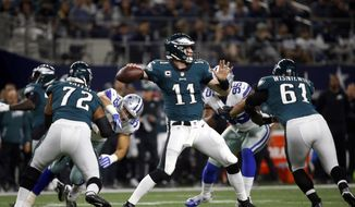 Philadelphia Eagles' Halapoulivaati Vaitai and Stefen Wisniewski (61) protect as quarterback Carson Wentz (11) throws a pass in the first half of an NFL football game against the Dallas Cowboys on Sunday, Nov. 19, 2017, in Arlington, Texas. (AP Photo/Ron Jenkins)