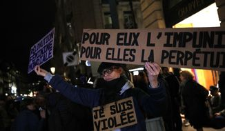 """FILE -  A Tuesday, Nov. 14, 2017 file photo of an activist holding a banner reading: """"For him impunity, for her a life sentence"""" during a protest in Paris. Justice Minister Nicole Belloubet provoked consternation by suggesting a legal minimum age of 13 for sexual consent """"is worth considering."""" Activists protested in Paris to demand that the age of consent be set at 15.  (AP Photo/Christophe Ena, File)"""