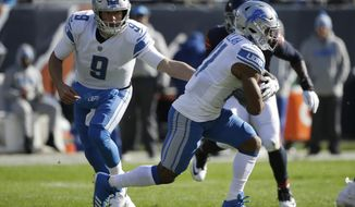 Detroit Lions quarterback Matthew Stafford (9) hands off the ball to running back Ameer Abdullah (21) during the first half of an NFL football game against the Chicago Bears, Sunday, Nov. 19, 2017, in Chicago. (AP Photo/Nam Y. Huh)