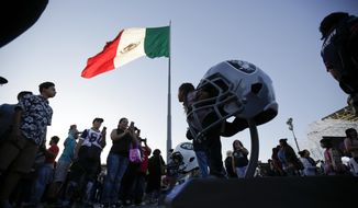 A girl poses inside a giant Oakland Raiders helmet during NFL football's Fan Fest in Mexico City's main square, the Zocalo, Saturday, Nov. 18, 2017. Thousands of football fans descended on the city's historic main plaza Saturday, one day before the New England Patriots face the Oakland Raiders in a football game at Aztec Stadium. (AP Photo/Gregory Bull)