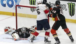 Anaheim Ducks goalie John Gibson (36) blocks a shot on goal as defenseman Josh Manson (42) and Florida Panthers center Aleksander Barkov (13) in the second period of an NHL hockey game in Anaheim, Calif., Sunday, Nov. 19, 2017. (AP Photo/Reed Saxon)