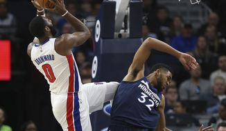 Detroit Pistons center Andre Drummond (0) shoots the ball after Minnesota Timberwolves center Karl-Anthony Towns fall back in the first half of an NBA basketball game, Sunday, Nov. 19, 2017, in Minneapolis. (AP Photo/Stacy Bengs)
