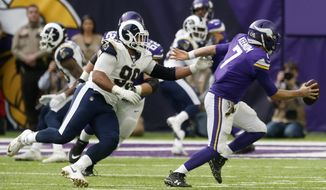 Minnesota Vikings quarterback Case Keenum (7) runs from Los Angeles Rams defensive end Aaron Donald (99) during the first half of an NFL football game, Sunday, Nov. 19, 2017, in Minneapolis. (AP Photo/Jim Mone)