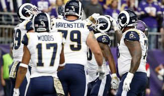 Los Angeles Rams running back Todd Gurley, center, celebrates with teammates after scoring on a 6-yard touchdown run during the first half of an NFL football game against the Minnesota Vikings, Sunday, Nov. 19, 2017, in Minneapolis. (AP Photo/Bruce Kluckhohn)