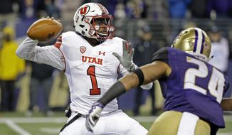 Utah quarterback Tyler Huntley (1) readies a pass as Washington defender Ezekiel Turner moves in during the first half of an NCAA college football game Saturday, Nov. 18, 2017, in Seattle. (AP Photo/Elaine Thompson)