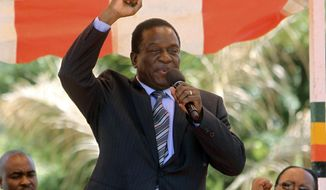 FILE - In this Wednesday Feb, 10, 2016 file photo, Zimbabwean vice President Emmerson Mnangagwa greets party supporters at the ZANU-PF headquarters in Harare. The ruling party's Central Committee confirmed Sunday, Nov. 19, 2017 that President Robert Mugabe has been fired as party leader and will be replaced by Mnangagwa. (AP Photo/Tsvangirayi Mukwazhi, File)