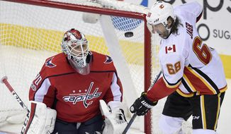 Washington Capitals goalie Braden Holtby (70) watches the puck next to Calgary Flames right wing Jaromir Jagr (68), of the Czech Republic, during the third period of an NHL hockey game, Monday, Nov. 20, 2017, in Washington. The Flames won 4-1. (AP Photo/Nick Wass)