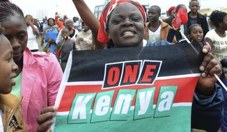 Supporters of Kenyan President, Uhuru Kenyatta, hold up a poster and celebrate in Nairobi Monday, Nov. 20, 2017, after Kenya's Supreme Court on Monday upheld President Uhuru Kenyatta's re-election in a repeat vote that the opposition boycotted while saying electoral reforms had not been made. The decision appeared to put an end to a months-long political drama never before seen in Africa that has left dozens dead. (AP Photo/John Muchucha)