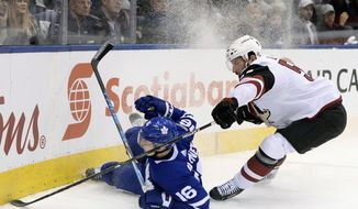 Toronto Maple Leafs center Mitchell Marner (16) loses his edge and falls in the corner as Arizona Coyotes defenseman Jason Demers (55) defends during first-period NHL hockey game action in Toronto, Monday, Nov. 20, 2017. (Nathan Denette/The Canadian Press via AP)
